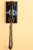 Old black telephone. With rotary disc on Yellow wall Stock Photos