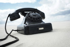 Retro vintage phone on the beach. Old black telephone on the beach Royalty Free Stock Image