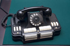 Old black telephone on green old table. Old black telephone on a table surface royalty free stock photography