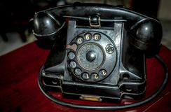 Old black telephone. Vintage black telephone on red wooden table. antique telephone Royalty Free Stock Image