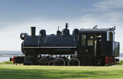 Old black train. On the green grass Stock Image