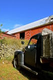 Old black truck in front of old red barn Stock Photo