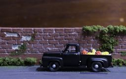 Old black truck on the road. Near the wall red brick Stock Photo