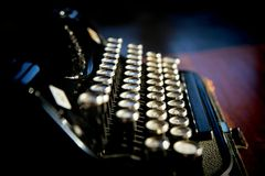 Old black typewriter. On dark background with shiny keys, side view Royalty Free Stock Photography