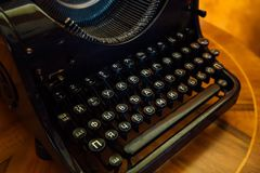 Old black typewriter with Russian Cyrillic letters on wooden table, close up stock photography