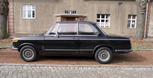 Old black vintage car parked in front of a house. Alongside a cobbled road in a close up side view Stock Photos
