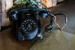 Old black vintage telephone on a table, Retro telecommunication in the old days. A old black vintage telephone on a table, Retro telecommunication in the old stock photos