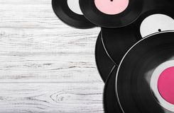 Old black vinyl records on white wooden background. vintage filtered. Copy space. Top view stock image