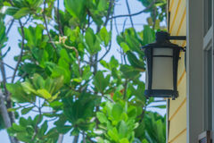 Old black wall lamp on wooden wall. Stock Photos