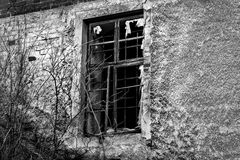 Old black and white damaged wall with a barred window Royalty Free Stock Photo
