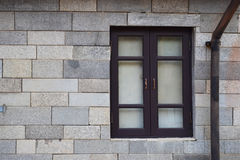 Old black window on white rock wall Stock Image