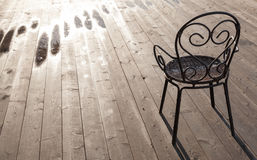 Old black wrought-iron chair standing on wooden floor Stock Image
