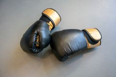 Old black and yellow boxing gloves on grey concrete background royalty free stock photo