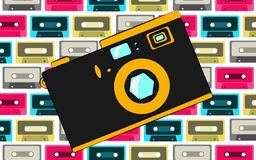 Old black and yellow retro vintage antique hipster obsolete camera on the background of a pattern of multi-colored audio cassettes. Vector illustration Royalty Free Stock Photo