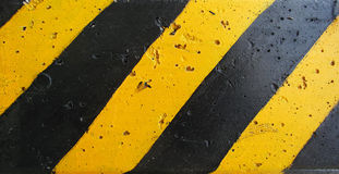 Old black and yellow strips on the wall Stock Photo