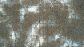 Old blackened mosaic surface. Aged tiled wall. Industrial background Royalty Free Stock Photos