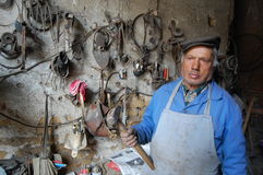 Old blacksmith with hammer in a hand poses at his workshop Royalty Free Stock Image