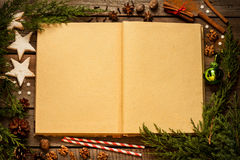 Old blank opened book with christmas decorations around on wood Royalty Free Stock Images