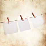 Old blank paper sheet hanging on a rope. On grunge background Royalty Free Stock Image
