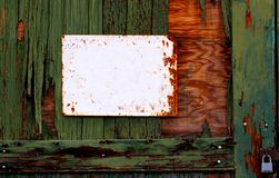 Old blank sign and green chipped paint wall. This old blank sign hanging on a green chipped paint wall waiting for your written copy. The image also has padlock royalty free stock photo