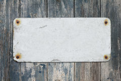 Old Blank Sign and Wall. Old corroded blank sign on faded painted wooden wall with space for copy royalty free stock photography