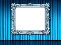 Old blank silver frame on blue velvet curtain Royalty Free Stock Photo