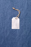 Old blank tag on fabric background Stock Image
