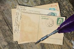 Old blank vintage postcard with old stamp is on old wood with nib Royalty Free Stock Photos