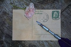 Old blank vintage postcard with old stamp is on old wood with pink rose and nib Stock Photo