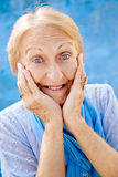 Portrait of surprised senior woman with hands on face on blue ba. Old blonde woman portrait, lady in elegant clothes with hands on face for joy and surprise on Royalty Free Stock Photography