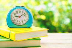 Old blue alarm clock on books. With blurred green natural background Stock Images
