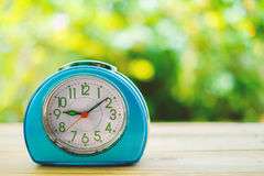 Old blue alarm clock on wooden table. With blurred green natural background Royalty Free Stock Photography