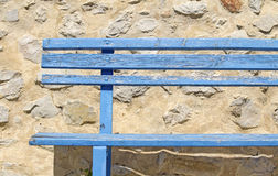 Old blue bench against rustic wall. Royalty Free Stock Photo