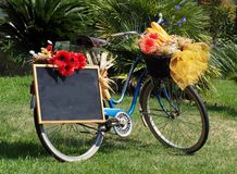 Old blue bicycle, adorned with flowers, with a blank black chalkboard, used as an advertising poster. You can add your text stock photo