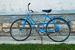 Old blue bicycle leaning against building wall Royalty Free Stock Image