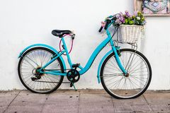 An old blue bike with flat tyres and flowers in the basket leaning against a white wall royalty free stock photography