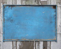 Old blue blank weathered wood noticeboard on rough dirty wall Stock Photography