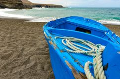 A blue boat on a black beach royalty free stock photography