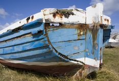 Old blue boat on shore. An un-seaworthy boat beached on the shore. Planks are coming loose Royalty Free Stock Images