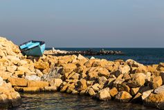 An old boat on the stones by the sea. The old blue boat is tied to the rocks by the sea Stock Image