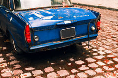 Old blue car standing on the street after the rain. In a puddle in autumn Stock Photos