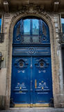 Old Blue carved ornate door in Paris, France. Antique wooden door of apartment building, outdoor. Vertical image royalty free stock image