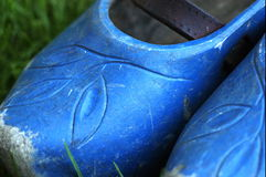 Old blue clogs. Pair of old blue clogs on grass background Stock Photo