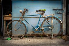 Old blue colored bicycle in a street Stock Photo