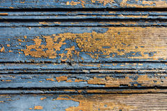 Old blue cracked paint on a orange wood door background Royalty Free Stock Photo
