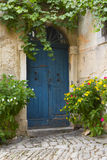 Old blue door. And flowers in pots Royalty Free Stock Image