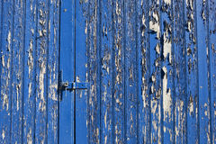 Old blue door. Background pattern and texture of an old wooden door with weathered blue paint and hasp and staple lock Stock Image