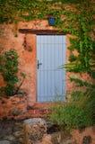 Old blue door in orange wall Stock Photography