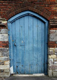 Old blue door in a wall Stock Image