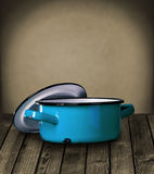 Old blue enameled pot on a wooden table Royalty Free Stock Photos
